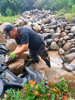 Matt adding rocks to walls of pond