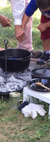 Student cooking with re-enactor volunteer