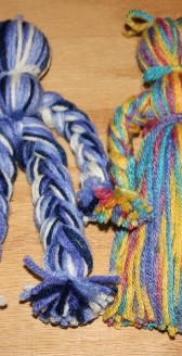 These yarn dolls are easy to make, if you can braid.  None of the kids I helped could braid but a few started to get the hang of it and one girl took home three extra strands of yarn to practice.