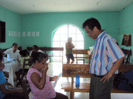 Byron helps with fitting glasses on woman in Chapab