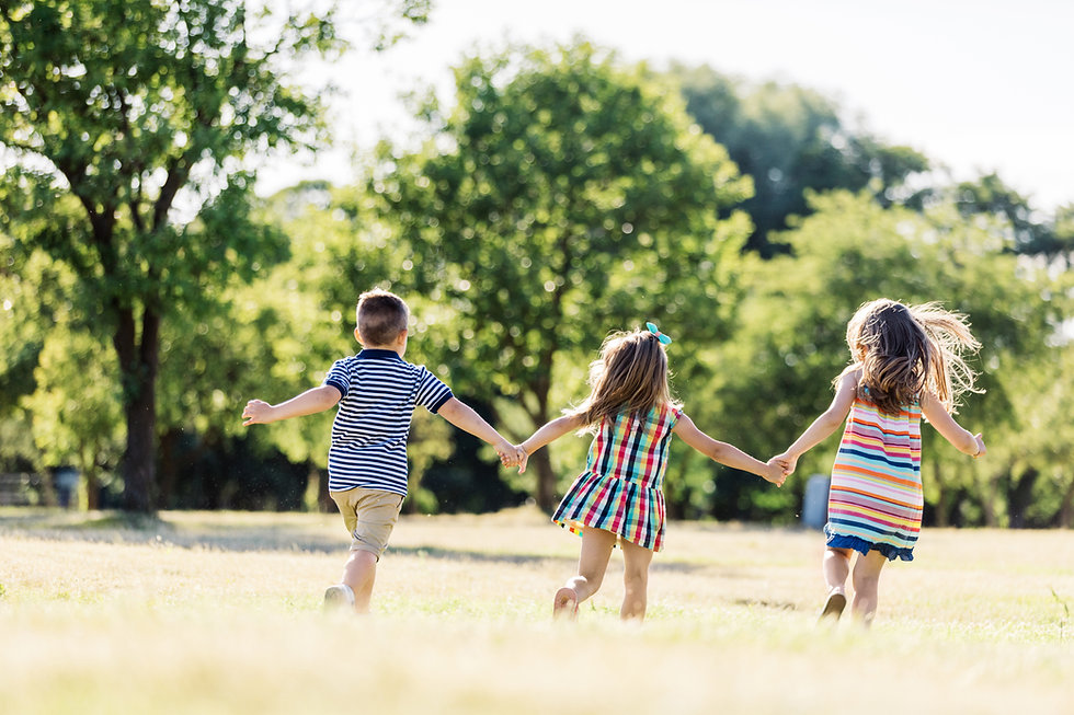 three-little-children-running-on-a-green
