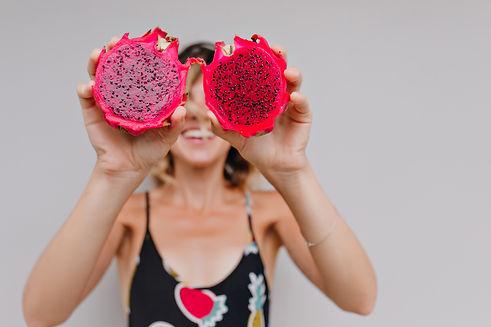 pretty-tanned-girl-holding-red-pitaya-po