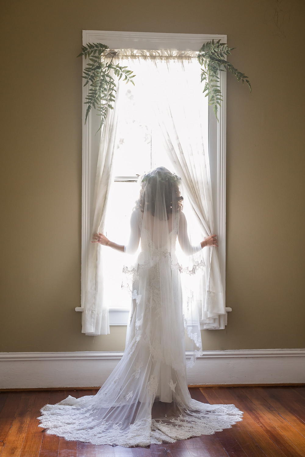 Fort Benning rustic chic bride stands in front of historic mansion window in Downtown Columbus Georgia.