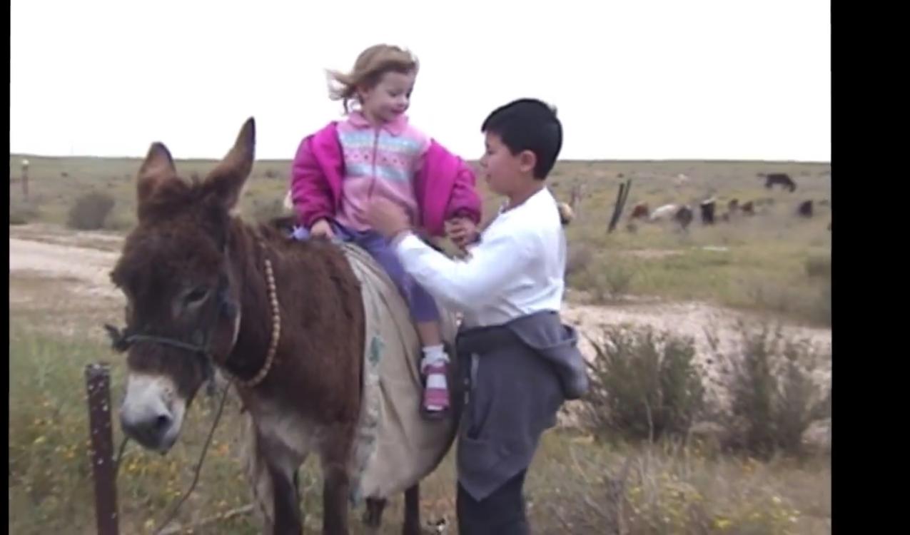 Little Liat riding donkey in desert