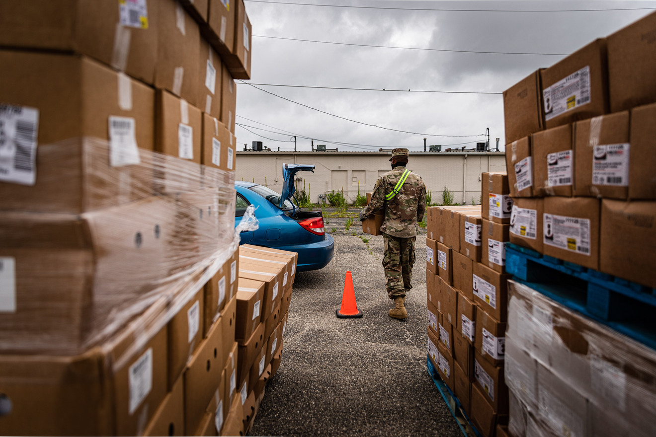 Indiana National Guardsmen, SPC Christopher Hamrick, assigned to A Co. 113th BSB delivers packages of food to the vehicle at the Five Points Mall's parking lot in Marion, IN. on June 23, 2020. The Indiana National Guard was activated to support the food banks throughout Indiana, in response to COVID-19