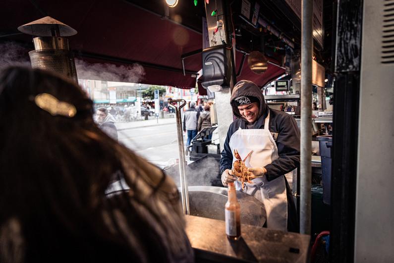 Street photo of a food vendor preparing to cook a crab at San Fransico, CA.