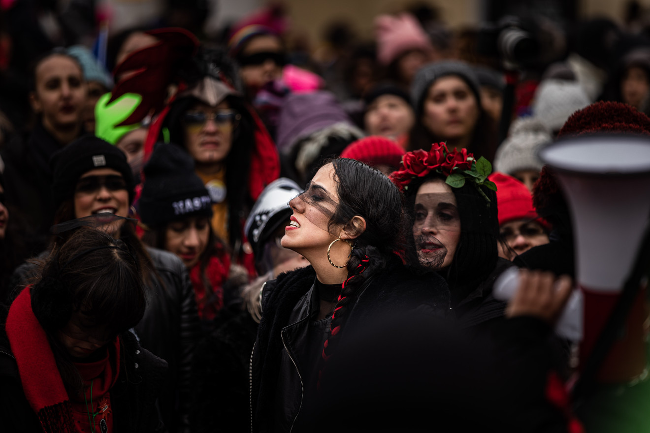 "A woman stands in front of the crowd, as the march itself is about the chant ""El violador eres tu"" in front of the White House in Washington, D.C. on Jan. 18, 2020. The song/dance originated in Chile and was to raise awareness of violence against women."
