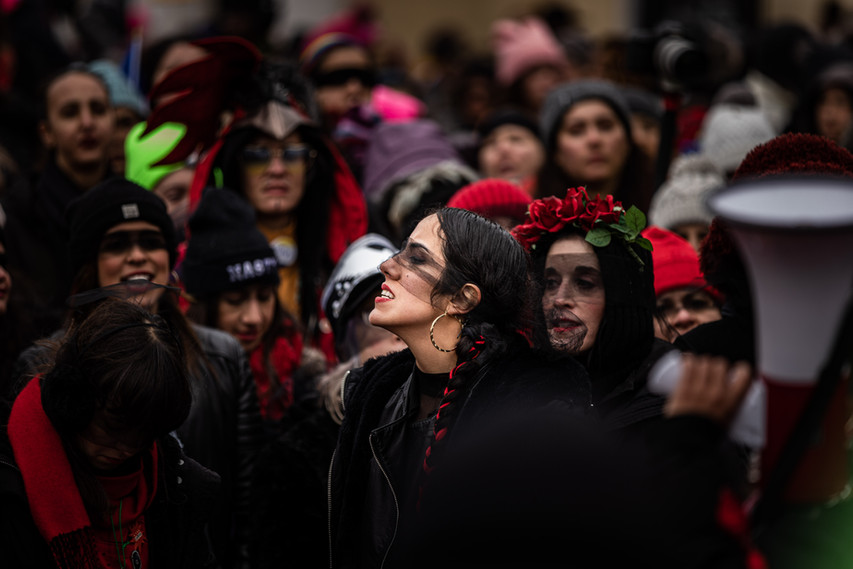 """A woman stands in front of the crowd, as the march itself is about the chant """"El violador eres tu"""" in front of the White House in Washington, D.C. on Jan. 18, 2020. The song/dance originated in Chile and was to raise awareness of violence against women."""
