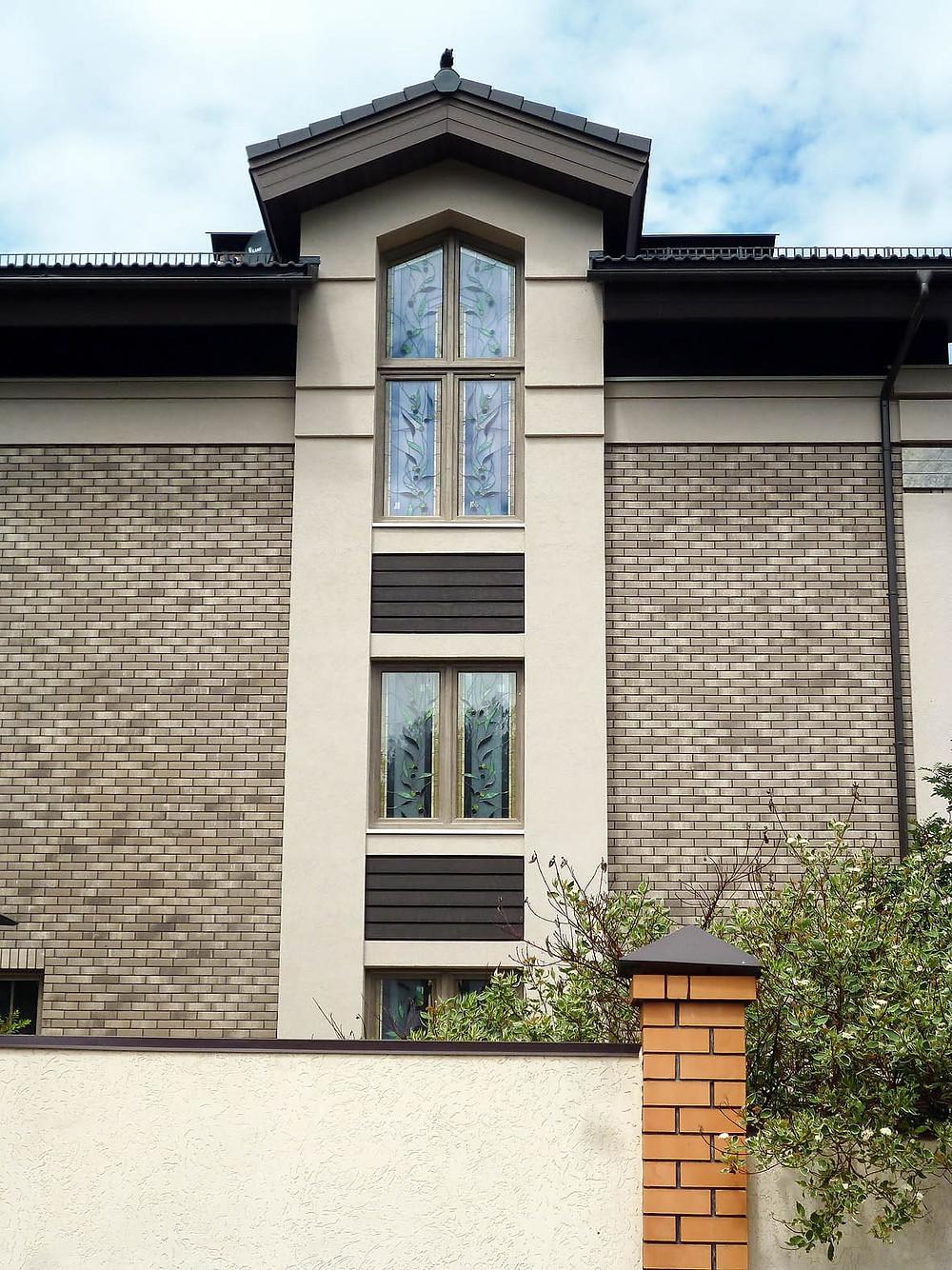 Витраж с оливковой ветвью на фасаде частного коттеджа