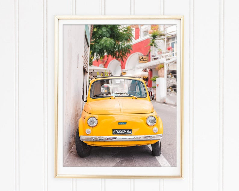 Yellow Fiat parked against a wall on the streets of Positano Italy