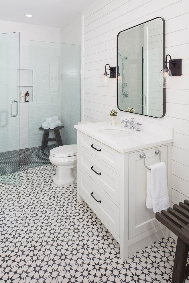 bathroom white vanity shiplap walls black mirror with sconces chrome hardware walk in shower star patterned tile floor black shower tile white subway tile wood bench with towels