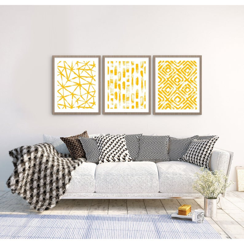 Tryptic collection of grey framed yellow abstract art with grey couch black and white throw pillows and blaket with area rug coffee cup vase with baby's breath and wooden plank floors