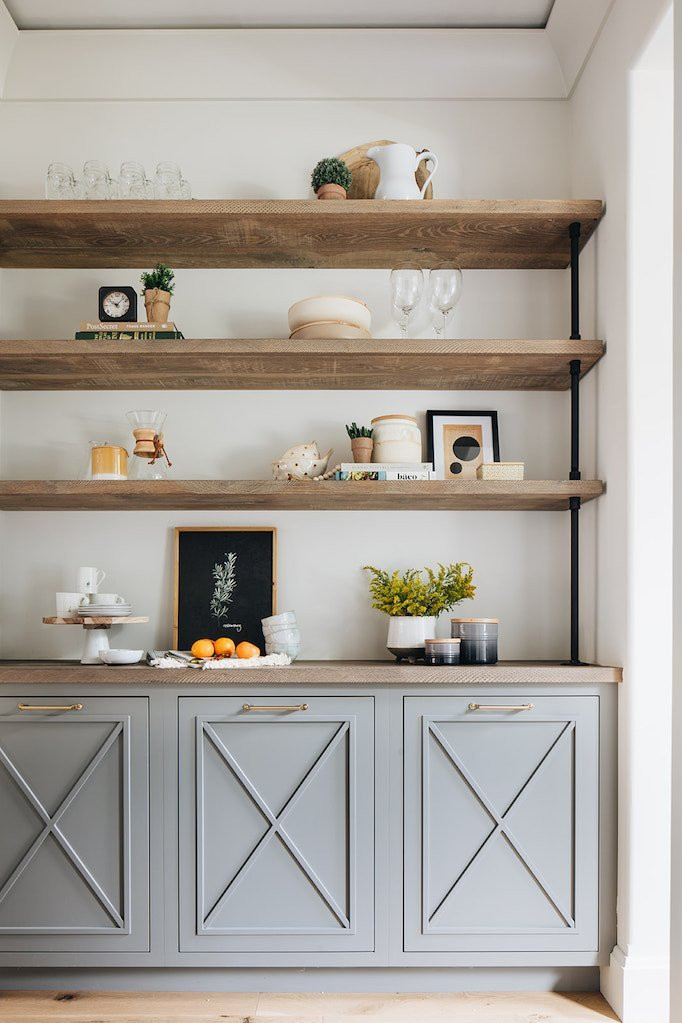 rustic wood farmhouse industrial shelving with grey lower cabinets with x detail mason jar glasses cake stand with mugs and plats framed prints with natural light and wood flooring