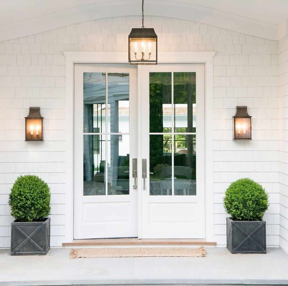 white shaker exterior with double white glass doors two light wall sconces oil rubbed bronze hanging pendant light over entrance straw mat boxwood plant in concrete grey pots