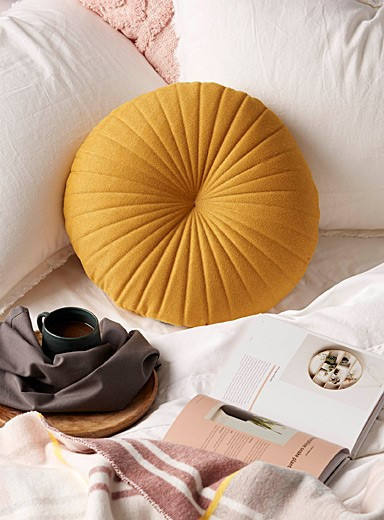 scalloped yellow throw cushion on bed with coffee and magazine