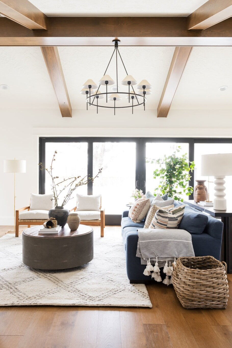 vaulted ceiling with wood details black framed accordion patio doors natural light wool area rug oversized blue sofa with throw pillows and throw basket on floor white table lamp floor lamp with two sitting chairs concrete grey ottoman oversized chandelier