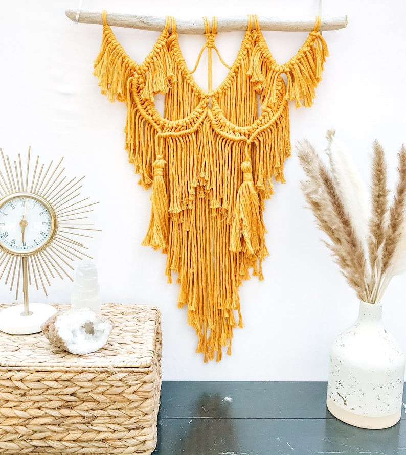 Yellow macramé wall hanging on driftwood with starburst clock vase woven rattan basket geode on dark wood shelf