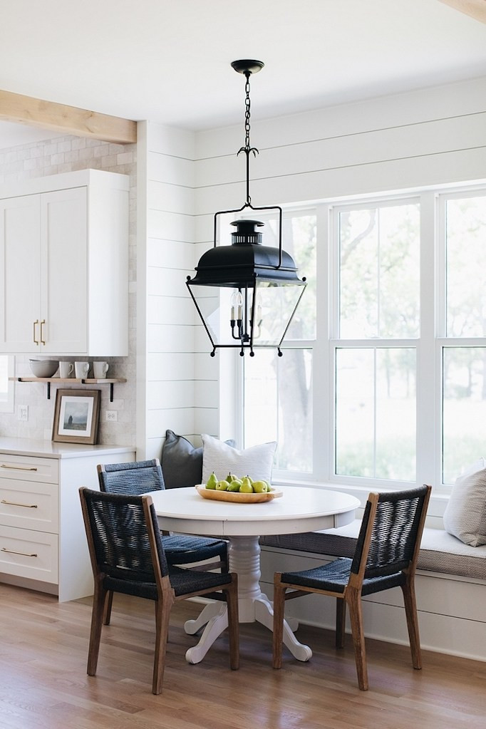 Kitchen nook with shiplap detail banquet seating round white table with three dark wood chairs with blue woven seats large black lantern pendant natural light windows kitchen eating area wood floors