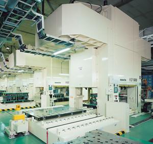 Uma linha de prensas-servo da série Komatsu H2F estampa chapas perfuradas para painéis de TVs de plasma. Esta prensa é programada para estampar cada peça com vários estágios, eliminando a necessidade de uma configuração tradicional de ferramenta progressiva.