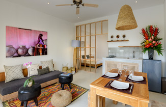 Living and dining area with bedroom in the background