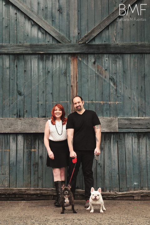 Couple and their two dogs posed in front of oversized wood doors.