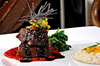 Stacked braised short ribs on a red toma