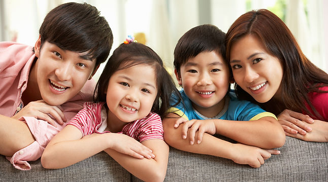 Chinese Family Sitting And Relaxing On Sofa Together At Home.jpg