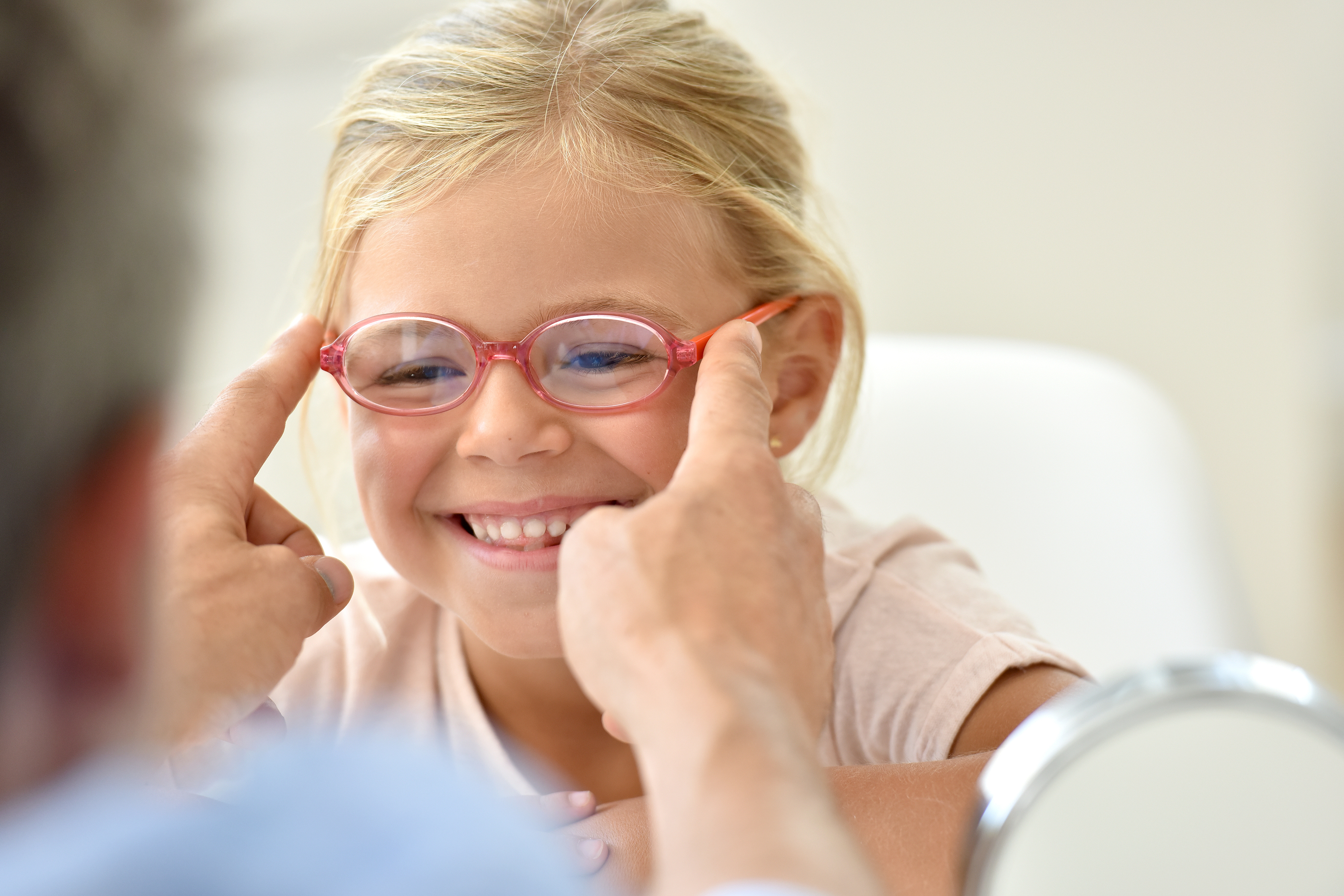 Little girl at the optician trying different eyeglasses