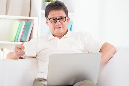 Portrait of mature Asian man using compu
