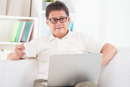 Portrait of mature Asian man using compu