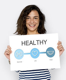 Smiling woman holding sign which says healthy
