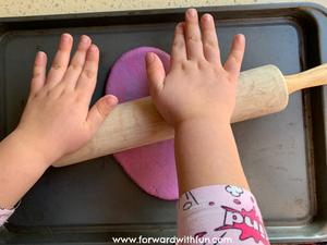 Child rolling out a purple dough