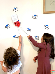 2 kids using fly swatters to hit AT words on a white wall and smiling