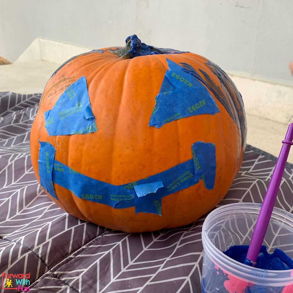 Paint a pumpkin with a taped face