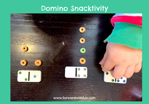 child's hand placing snacks to match the numbers on the dominoes