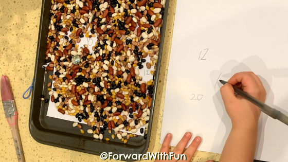 Child writing numbers on right side. Left side is a baking tray with beans on it, hiding numbers underneath