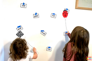2 kids using fly swatters to hit words that are part of the AT word family: pat, bat, mat, hat, etc