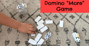 """child playing """"more"""" game with dominoes"""