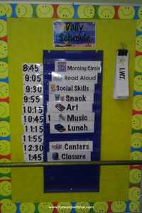 Environmental print example of a visual daily schedule on a classroom door. Shows the times of the different activities: morning circle, read aloud, social skills, snack, art, music, lunch, centers, closure with pictures next to each thing