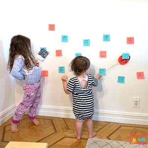 two child playing a game where they are hitting numbers and letters with fly swatters