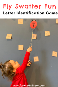 Toddler holding a fly swatter trying to reach a post it. Blue wall with many post its on it, all with alphabet letters on them