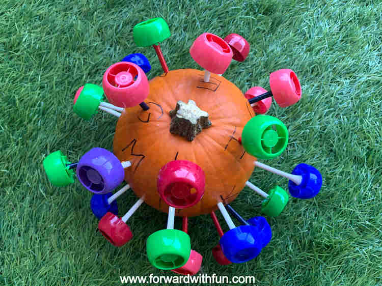 Pumpkin covered in golf tees and pouch caps