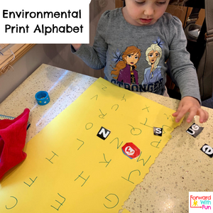child gluing letters from environmental print like magazines and food boxes onto a large yellow sheet of paper that has the alphabet letters written on it