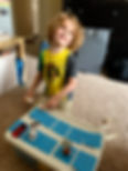 Young buy placing toys on matcing letters