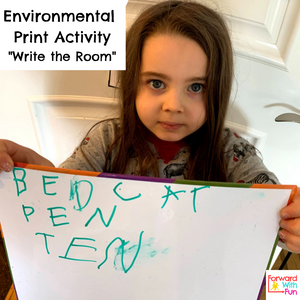 Child holding up a white board where she has written: bed, cat, pen, ten