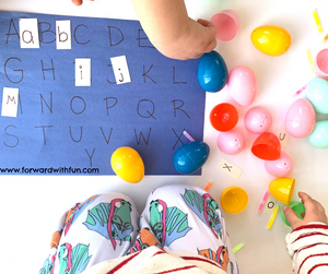 Preschooler hands matching letters to capital letters on a blue alphabet mat. Easter eggs that are open near the mat, have letters and glow sticks in them