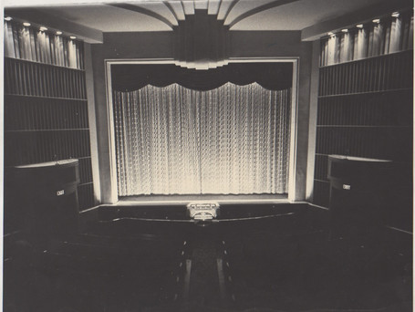This photograph was taken sometime between 1973 and 1979. A few noticable changes between this photograph and the modern-day Fargo Theatre include the missing neon fountains, a patterend main curtain, a more decorative upper curtain, and the two-manual console. At the time the photograph was taken, the stage only came as far out as the proscenium arch. In front of the stage was the original orchestra pit and rails.