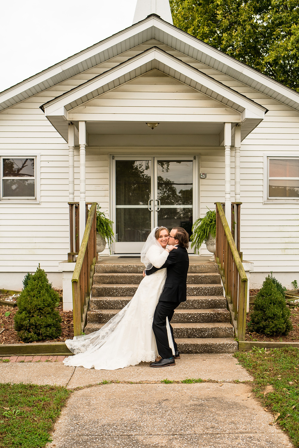 Groom picks up bride to kiss her
