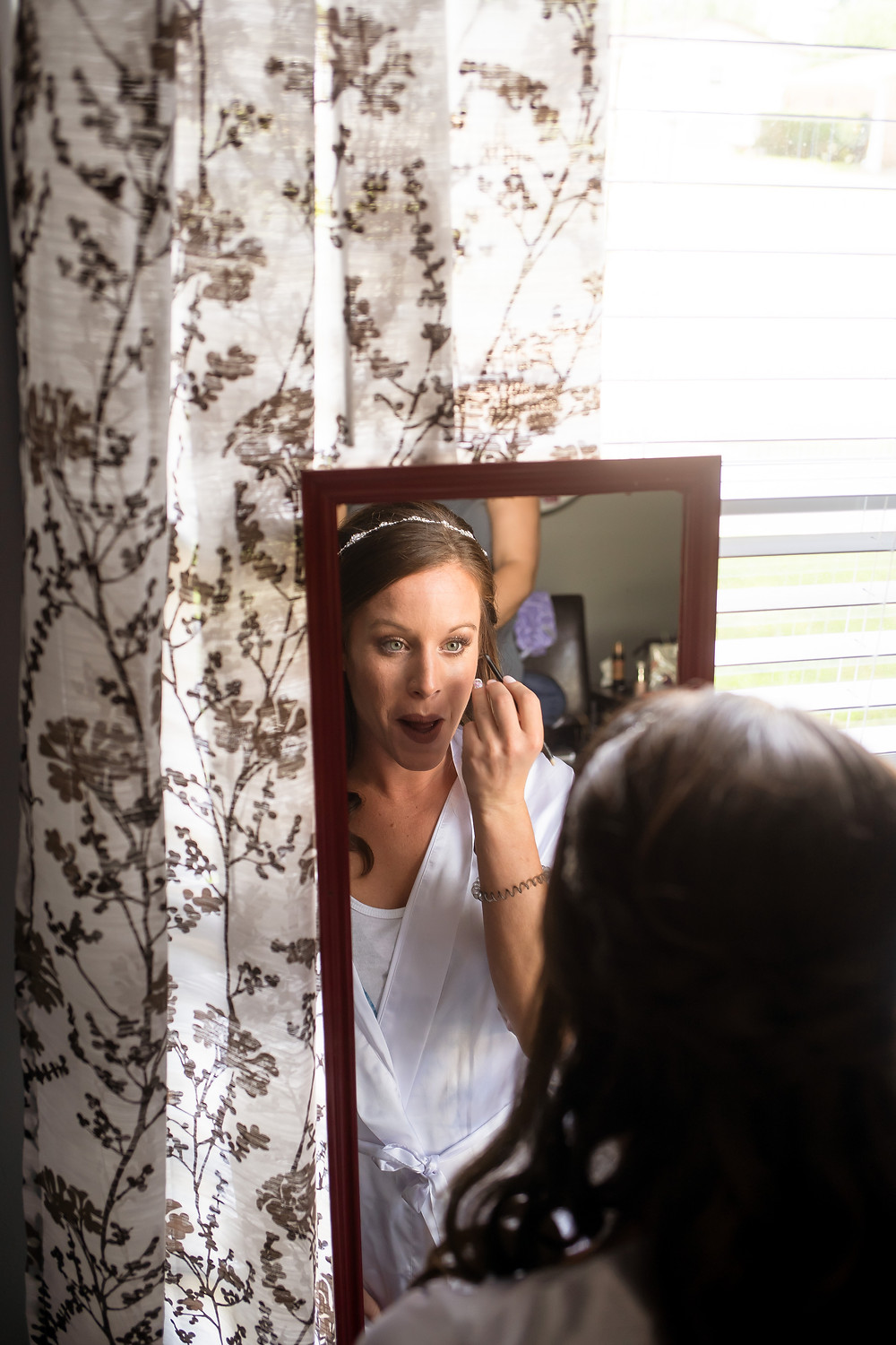 Bride looking in mirror and doing makeup