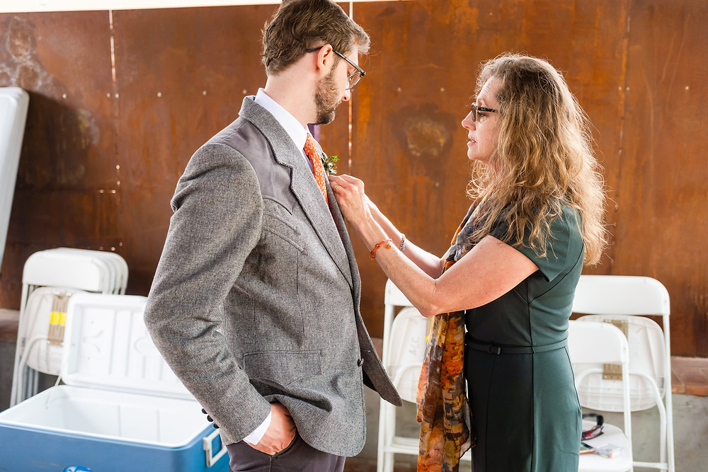 Mother putting boutonnière on son
